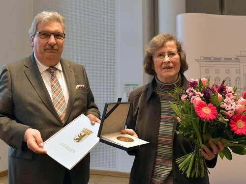 Ralf Wieland hält eine Urkunde in der Hand. Neben ihm eine Frau, die in der einen Hand einen Blumenstrauß und in der anderen eine Medaille trägt.