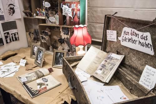 Kunstinstallation einer Ausstellung. Im Vordergrund ein offener Koffer mit Zetteln und Büchern.
