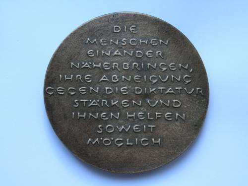 """Alte Münze mit der Beschriftung """"Die Menschen einander näherbringen, ihre Abneigung gegen die Diktatur stärken und ihnen helfen soweit möglich"""""""