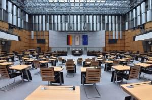 Der leere Plenarsaal mit Blick auf den Sitz des Präsidenten, die einzelnen Sitzeplätze sind auseinandergerückt