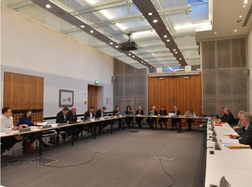 Man sieht einen großen Saal mit Tischen im Kreis angeordnet. Es tagt der Petitionsausschuss.