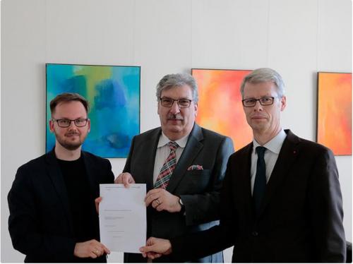 Zwei Mitglieder des Petitionsausschuss übergeben dem Präsidenten des Abgeordnetenhaus Berlin den Jahresbericht