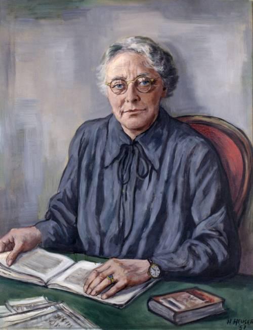 Gemälde einer älteren Frau, die an einem grünen Tisch auf einem roten Sessel sitzt. Sie hat eine blaue Bluse an, weißes Haar und trägt eine runde Brille. Vor ihr liegt ein geöffnetes Buch.