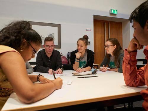 Schüler sitzen gemeinsam an einem Tisch und erarbeiten etwas