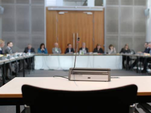 Ein leerer Sitz mit Mikrofon während einer Sitzung des Petitionsausschusses, im Hintergrund sieht man verschwommen andere Ausschussmitglieder