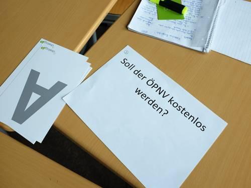"""Zettel auf einem Tisch. Darauf die Frage """"Soll der ÖPNV kostenlos werden?"""", daneben liegen Abstimmungskarten."""
