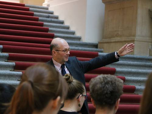 Ein Mann führt Besucher durch das Abgeordnetenhaus Berlin und zeigt dabei auf etwas