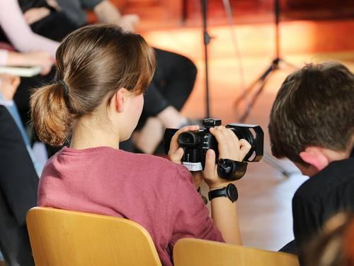 Man sieht eine junge Frau von hinten, die eine kleine Filmkamera hält