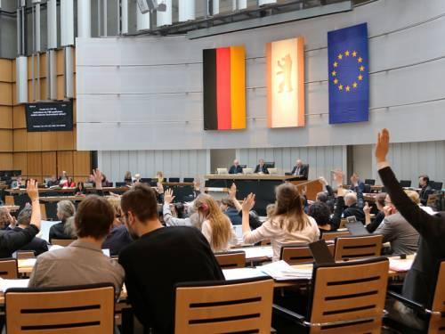 Blick in den Plenarsaal während einer Plenarsitzung. Abgeordnete heben die Hände zur Abstimmung.