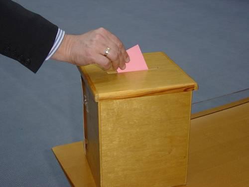 Eine Hand wirft einen rosa Wahlzettel in eine Urne