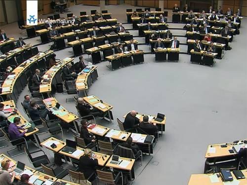 """Blick in den Plenarsaal mit Abgeordneten - oben ein kleines Logo von Alex TV und das Wort """"Wiederholung"""""""