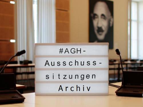 """Eine Lichtbox auf einem Tisch in einem Saal. Auf der Lichtbox steht """"#AGH - Ausschusssitzungen Archiv"""""""