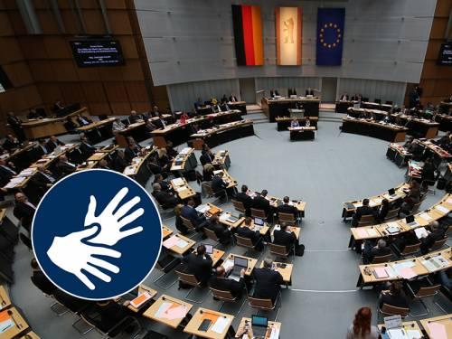 Blick in den Plenarsaal mit Abgeordneten, darauf das Symbol für Gebärdensprache
