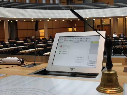 Blick in den Plenarsaal vom Sitz des Präsidenten aus, mit Sicht auf einen Monitor und eine Glocke