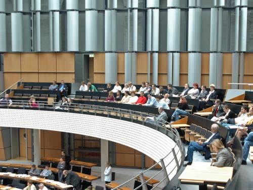 Besucherinnen und Besucher sitzen auf der Tribüne. Man sieht ein paar Abgeordnete im Plenarsaal.