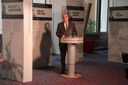 Ein Mann steht am Rednerpult, hinter ihm Plakate.