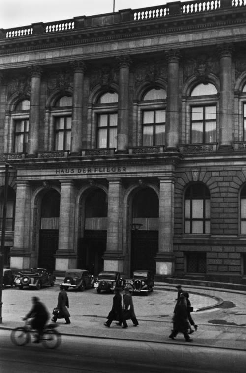 """Schwarz Weiß Aufnahme der Fassade des Abgeordnetenhaus Berlin. Im Vordergrund laufen Menschen und es parken Autos. Am Eingang sind große Buchstaben: """"Haus der Flieger"""""""
