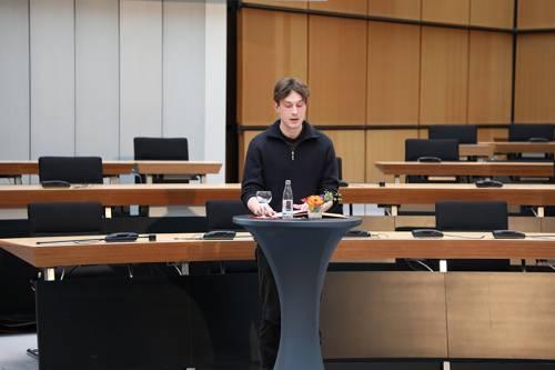 Ein Mann im schwarzen Pullover steht an einem Stehtisch und spricht.