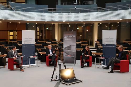3 Männer und eine Frau sitzen in roten Sesseln, zwischen ihnen stehen Plakate. Sie werden gefilmt.