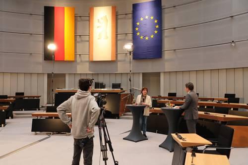 Eine Frau und eine Mann stehen an Stehtischen und unterhalten sich. Ein junger Mann steht vor ihnen mit einer Kamera und filmt.