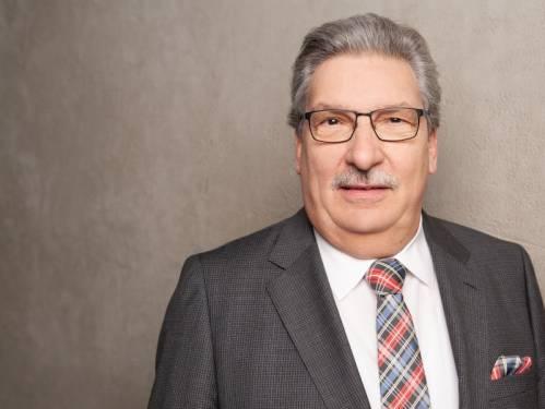 Ein älterer Mann im grauen Anzug und karierter Krawatte vor einem braunen Hintergrund. Er hat graue Haare, einen Schnurrbart und trägt eine Brille.