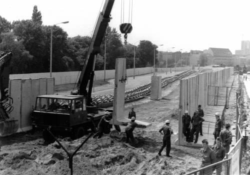 Schwarz Weiß Foto eines Baggers, der weitere Mauerstücke anbringt. Bauarbeiter helfen das Stück auszurichten.