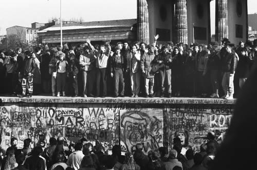 Schwarz Weiß Foto von Menschen, die auf und vor der Mauer stehen. Sie jubeln teilweise.