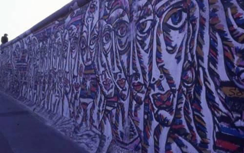 Graffiti von Gesichtern auf der Berliner Mauer, das Bild wirkt lila.