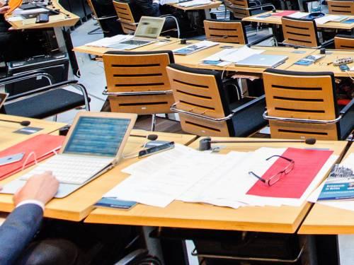 Tische im Plenarsaal. Man sieht eine Hand an einem Laptop und viele Unterlagen.