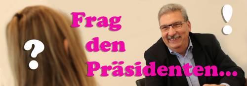 """Der Präsident Ralf Wieland. Vor ihm sitzt eine Schülerin. Auf dem Bild sieht man Fragezeichen und """"Frag den Präsidenten"""""""