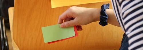 Notizzettel in der Hand eines Kindes