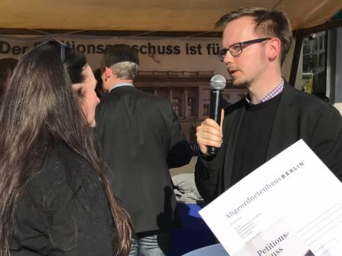 Links sieht man eine Frau mit langen braunen Haaren. Sie steht vor einem Mann, der in ein Mikrofon spricht.